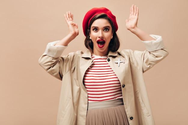 Signora dagli occhi marroni in trincea alla moda sguardi sorpresi nella fotocamera. donna scioccata in maglione a righe, gonna beige e cappotto in posa su sfondo isolato.