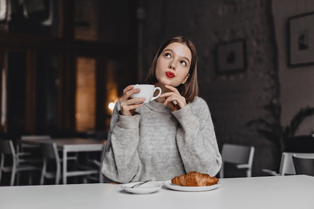 Brown-eyed lady with red lipstick posing thoughtfully with cup of tea. woman in gray sweater sitting at table with croissant.