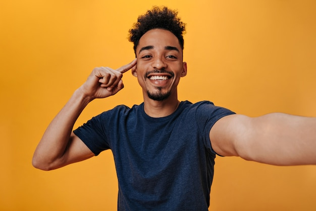 Brown-eyed man in blue t-shirt with smile makes selfie on orange wall