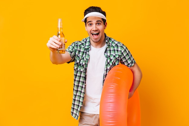 Brown-eyed man in white cap and plaid shirt laughs against orange space. portrait of guy on vacation with inflatable circle and bottle of beer.