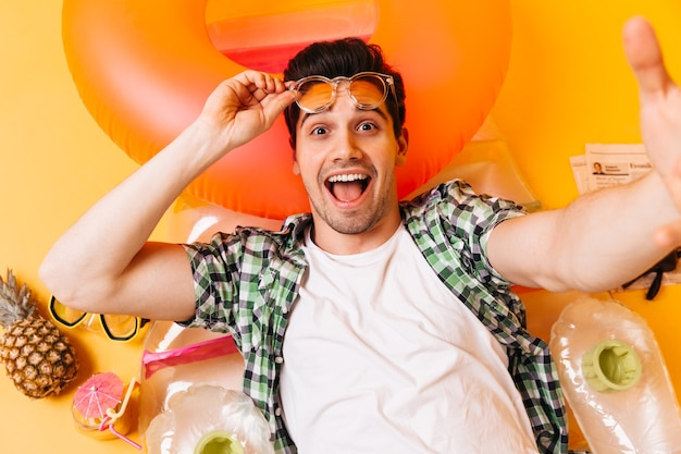 Brown-eyed man in white t-shirt and plaid shirt takes off his sunglasses and takes selfie on inflatable mattress.