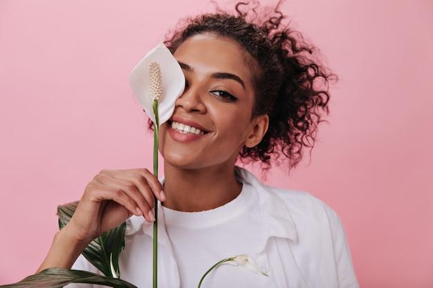 茶色の目の女性は大きな花で顔を覆っている