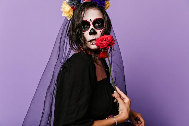 미망인 복장을 한 갈색 눈의 여성이 큰 빨간 장미를 보여줍니다. 검은 옷에 특이한 메이크업을 한 갈색 머리의 스냅 샷.