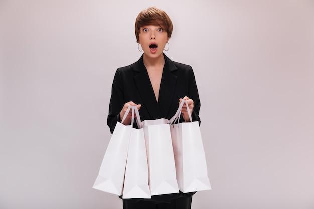 검은 양복에 갈색 눈동자 여자는 놀람에 카메라에 보이는 쇼핑 가방을 보유하고 있습니다. 어두운 재킷에 충격 된 짧은 머리 소녀는 고립 된 패키지와 함께 포즈