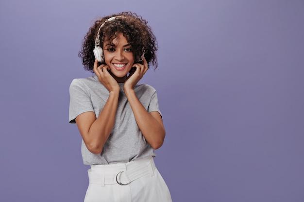 紫色の壁に笑みを浮かべて白いヘッドフォンで茶色の目の女性