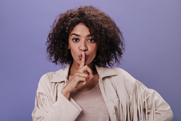 Brown-eyed woman in jacket with fringe asks to observe silence. portrait of curly girl in beige outfit who keeps secret