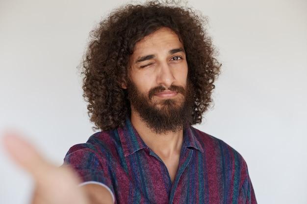 Giovane barbuto dagli occhi castani con i capelli scuri ricci che sbatte le palpebre mentre si fa una foto, in piedi in camicia casual
