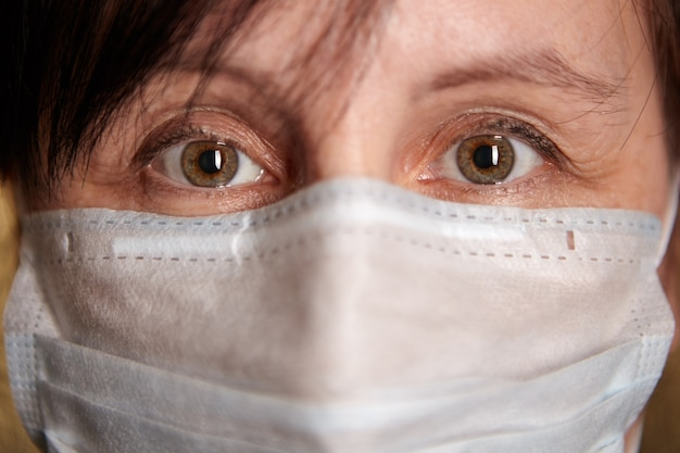 Covid-19 대유행 중 얼굴 보호 마스크 위에있는 중년 여성의 갈색 눈.