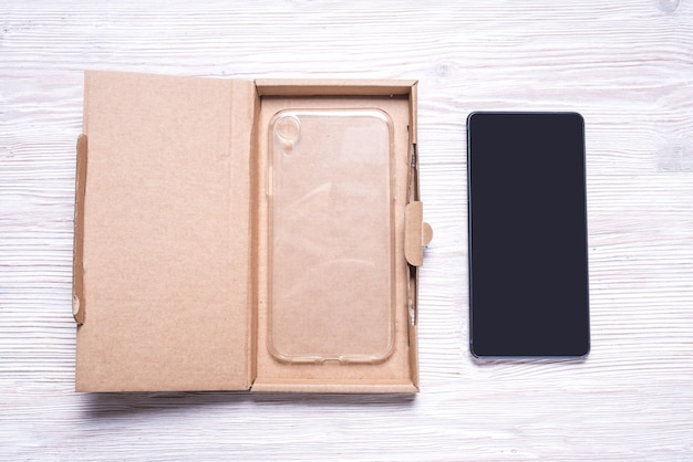 Brown flat cardboard box for cellphone, smartphone case packaging.