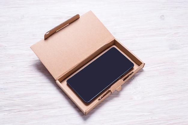 핸드폰, 스마트 폰 케이스 포장용 갈색 평면 골판지 상자.