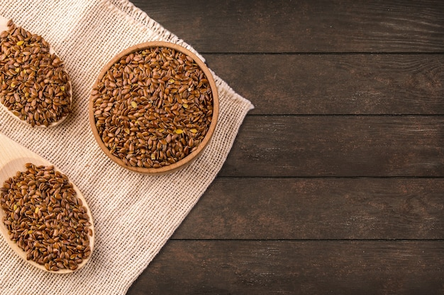 The brown flax seeds or flax seed in a small bowl on sacking and two wooden false on a brown wooden table photographed from above