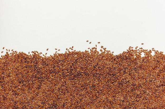 흰색 테이블에 흩어져있는 갈색 아마 씨앗