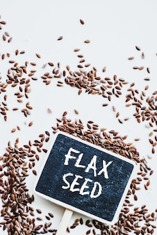 Brown flaxseed or linseed and chalkboard with phrase flax seed