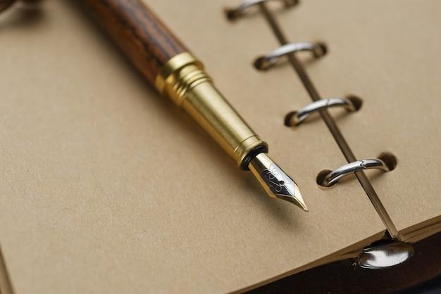 イエローページのノートに茶色の万年筆。