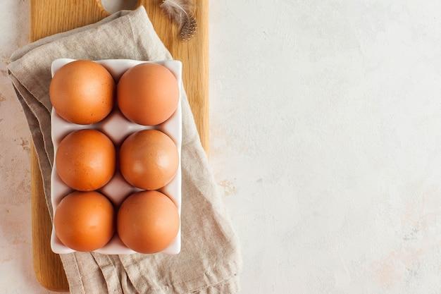Коричневые свежие яйца в стойке на крупном плане деревянной доски. понятие о сельскохозяйственных продуктах. всемирный день яиц 9 октября. плоская кладка. фото высокого качества
