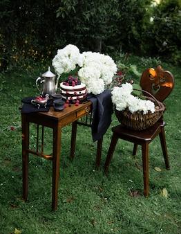 庭の狭い木製のテーブルに茶色のフルーツケーキ。シルバーティーポットと2杯のブラックティーが構成を補完しています。
