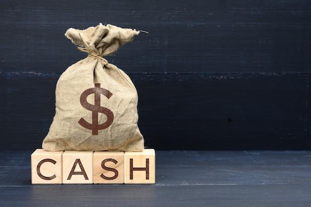 Коричневая полная холщовая сумка с символом доллара и деревянными кубиками с надписью cash
