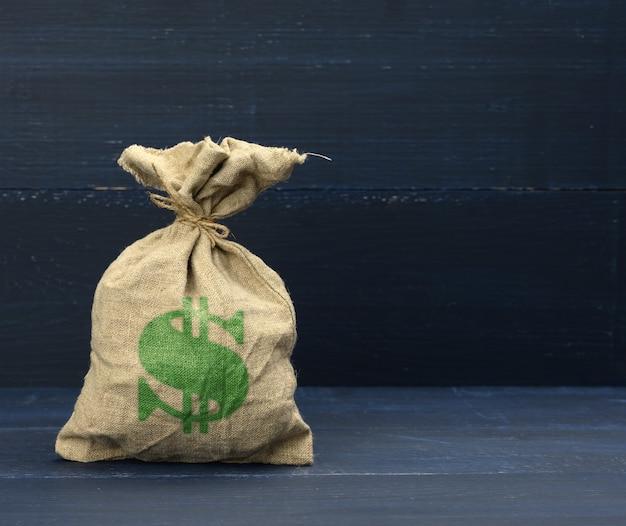 Коричневая полная холщовая сумка с символом доллара на синей поверхности