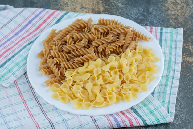 Brown fusilli pasta and farfalle pastas in the bowl on the towel, on the marble background.