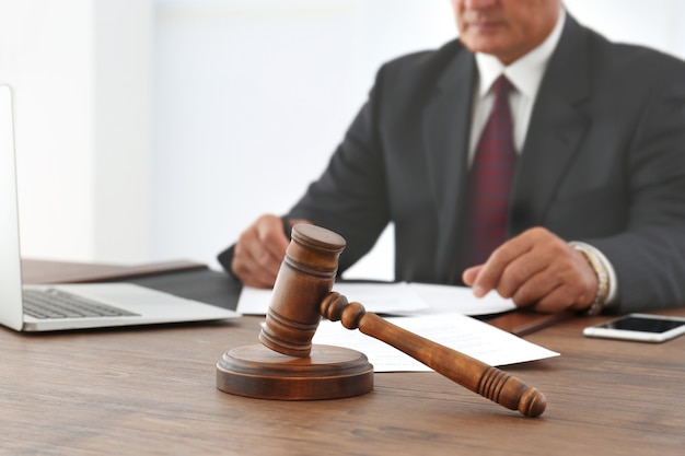 Brown gavel on wooden table and male lawyer