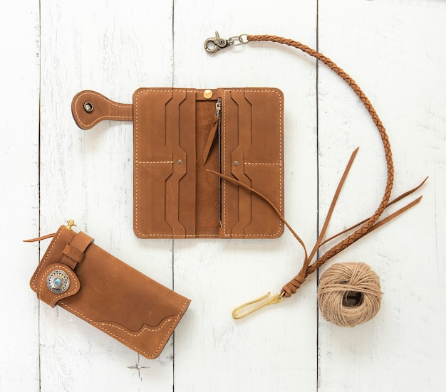 Brown genuine leather wallets accessory isolated on wooden background. top view.