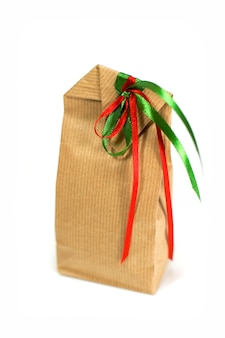 Brown gift bag with ribbons isolated on white background