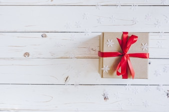 Brown gift box and Christmas presents on white wooden table background.