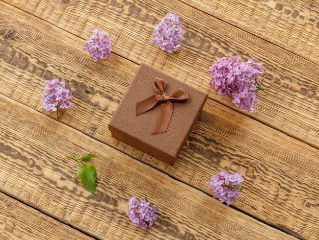木の板に茶色のギフトボックスとライラックの花。上面図。グリーティングカードのコンセプト。