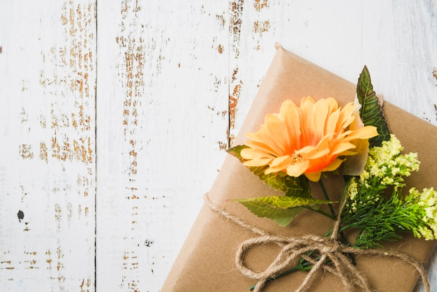 Above brown gift box decorated with flowers on wooden textured backdrop