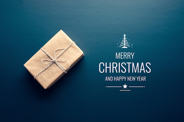 Коричневая подарочная коробка в сделанном своими руками и с рождеством христовым текстом на темном фоне. подарки и юбилейные подарки. вид сверху