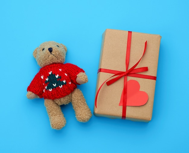 Brown gift box and little brown teddy bear on a blue background