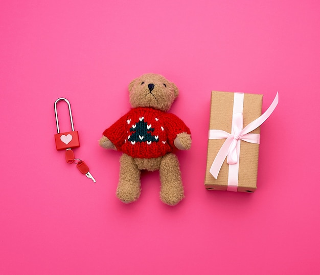 Brown gift box and little brown teddy bear on a pink background,
