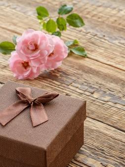 Коричневая подарочная коробка на старых деревянных досках, украшенная розовыми розами. вид сверху.