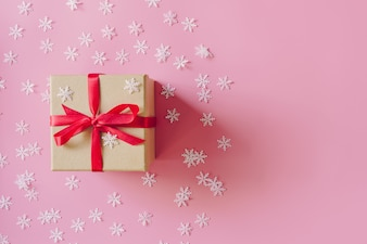 Brown gift box on the pink background with christmas decoration.