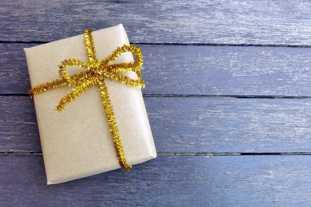 A brown gift box tied with a golden bow on the brown wooden background