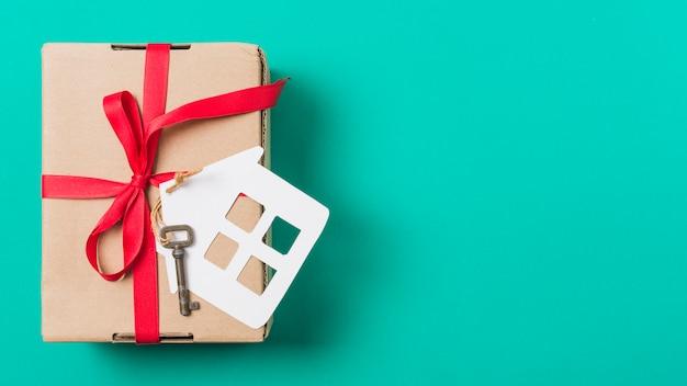 빨간 리본으로 묶어 갈색 선물 상자; 청록색 표면 위의 집 열쇠