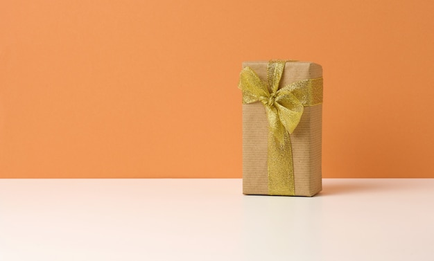 Brown gift box on white table, orange background, surprise and gift. copy space