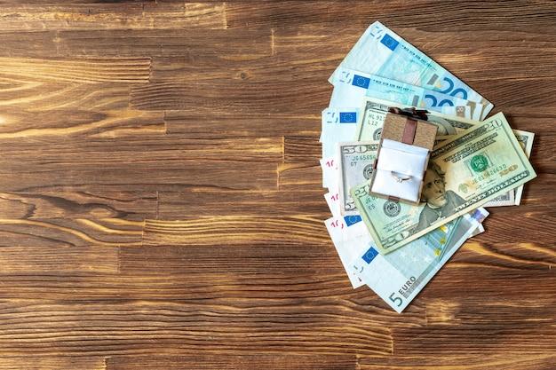 Коричневая подарочная коробка с золотыми украшениями кольца и банкнотами долларовых купюр на деревянном столе. покупка сюрприз, подарок за деньги, концепция наличных денег, вид сверху, копировальное пространство.