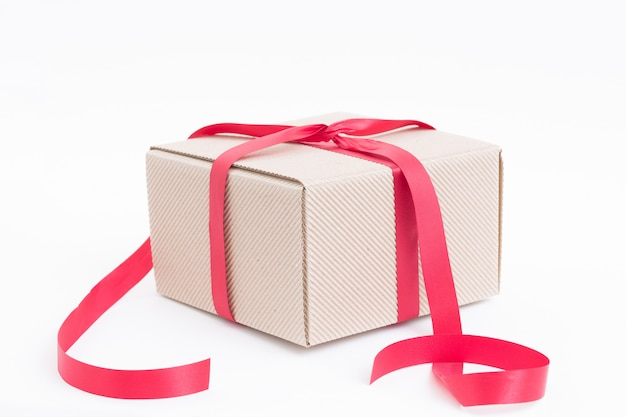 Brown gift box with red ribbon on white