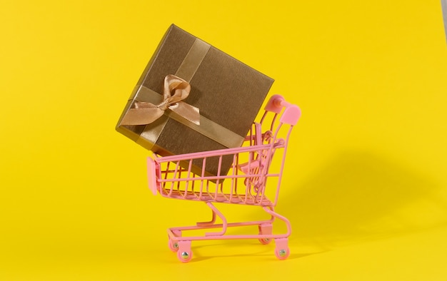 Brown gift box with a silk bow in a miniature metal trolley on a yellow background. party backdrop, surprise, seasonal sale
