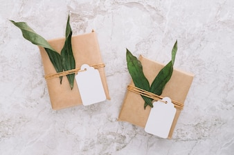 Brown gift boxes with blank tag and leaves on marble backdrop