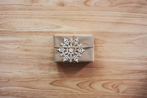 Above brown gift and christmas decoration on wooden background