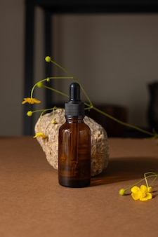 Brown glass bottle of cosmetic product or oil on stone and yellow wildflower on beige brown paper ba...