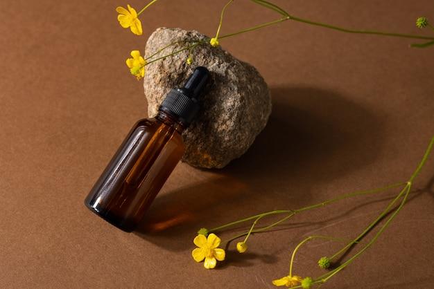 Коричневая стеклянная бутылка косметического продукта или масла на камне и желтом полевом цветке на бежевом фоне коричневой бумаги. концепция косметической красоты natura spa с твердыми тенями, вид сбоку
