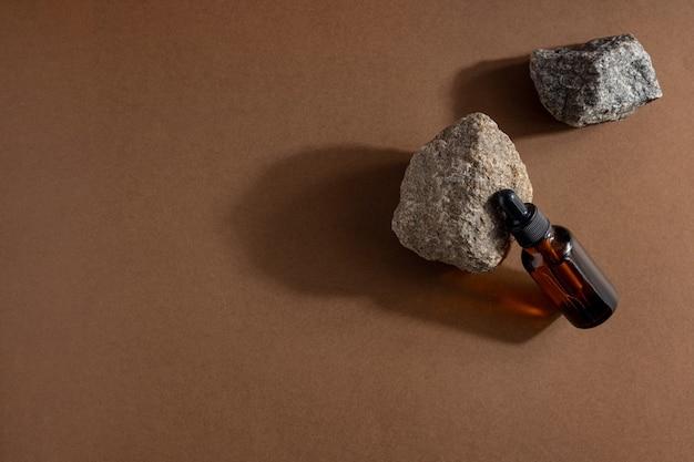 Коричневая стеклянная бутылка косметического продукта или масла на камне на бежевом фоне коричневой бумаги. концепция косметической красоты natura spa с жесткими тенями copyspace