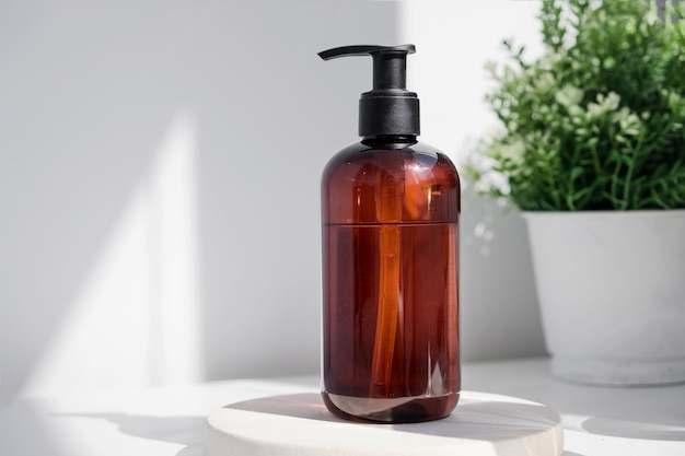 肌のための軽いエコ化粧品クリーム血清の朝の光線の白い表面に茶色のガラス瓶