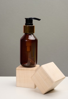 Brown glass bottle with black pump of cosmetic products on wooden block. natural organic spa cosmetic, beauty concept. mockup