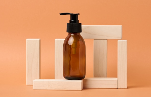 Brown glass bottle with black pump of cosmetic products on wooden block on a orange paper background. natural organic spa cosmetic, beauty concept. mockup