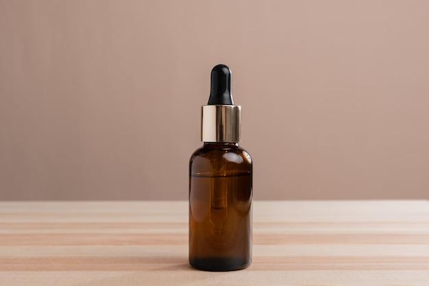 ベージュとウッドの背景に分離されたピペット付きの茶色のガラス ボトル