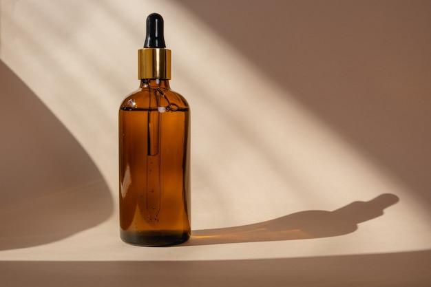 太陽の影で白い背景に分離されたピペット付きの茶色のガラス瓶